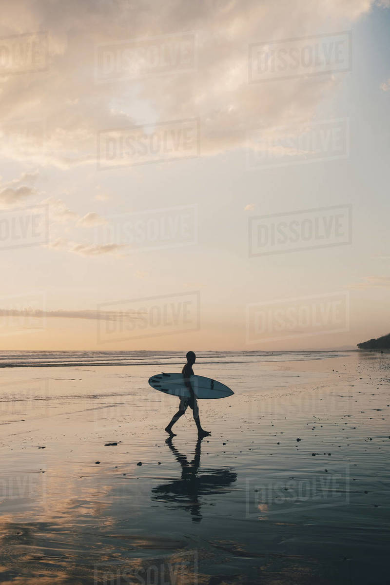 Silhouette man with surfboard walking at beach during sunset Royalty-free stock photo