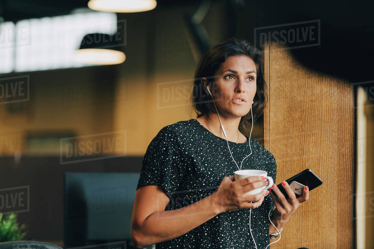 Female executive holding coffee cup while talking with earphones during phone call in office Royalty-free stock photo