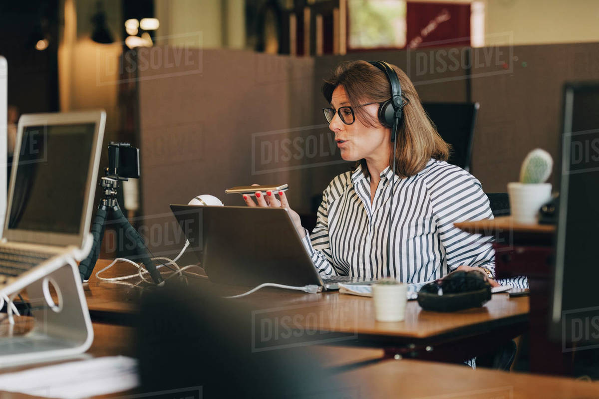 Mature businesswoman wearing headphones while talking on mobile phone in office Royalty-free stock photo