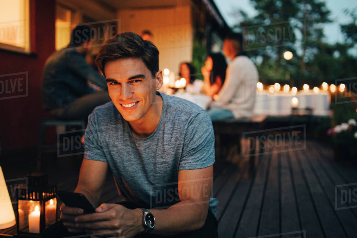 Portrait of smiling young man holding smart phone while friends in background during dinner party Royalty-free stock photo
