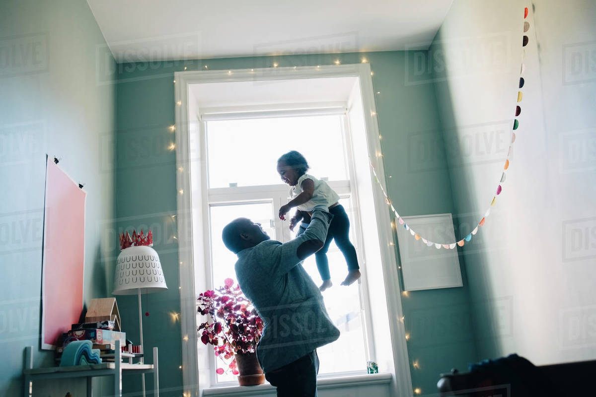 Side view of happy father holding daughter while standing by window at home Royalty-free stock photo