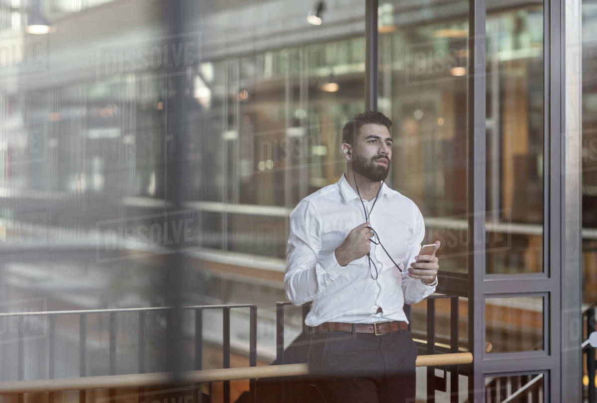 Businessman wearing headphones and using smart phone while standing in lobby at office Royalty-free stock photo