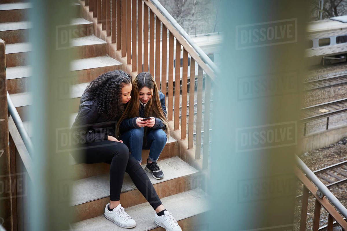 Teenage girl showing mobile phone to female friend while sitting on steps Royalty-free stock photo