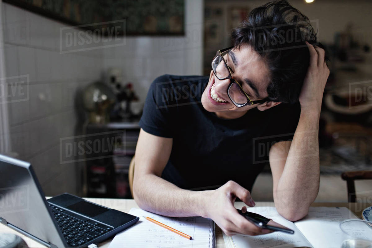 Cheerful social media addicted young man using mobile phone while doing homework Royalty-free stock photo