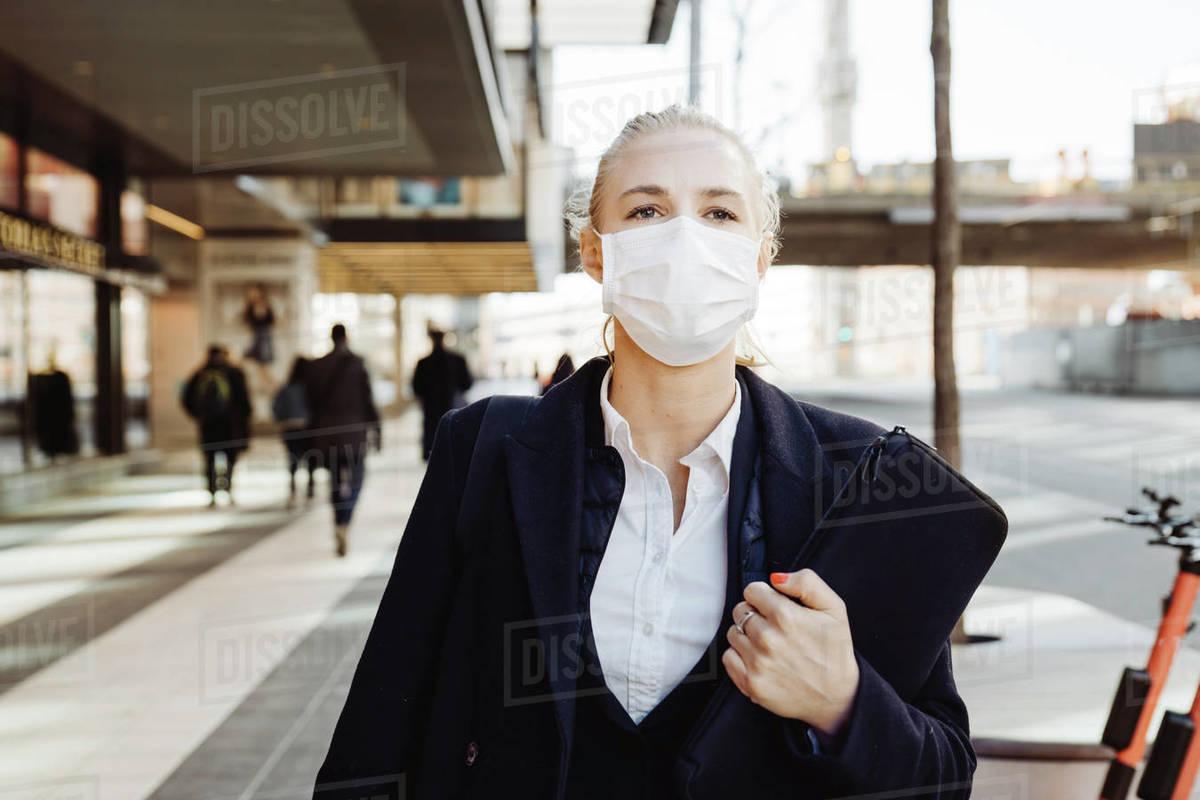 Businesswoman walking in street wearing face mask Royalty-free stock photo
