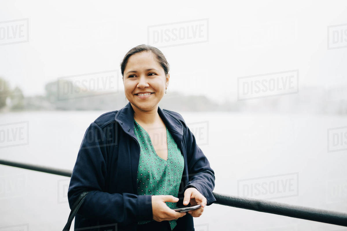 Smiling female entrepreneur with phone standing against sea in city Royalty-free stock photo
