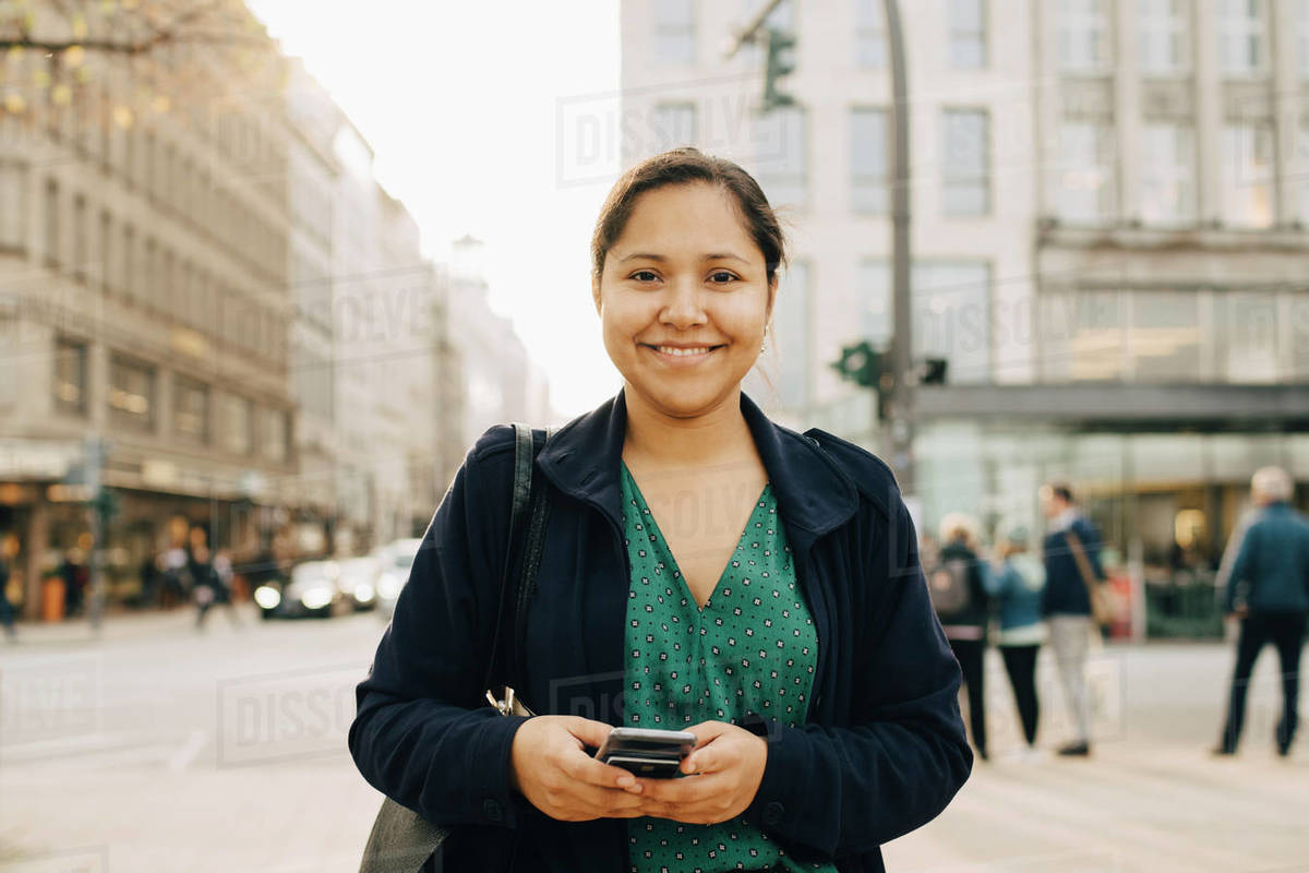 Portrait of smiling female entrepreneur with phone standing in city Royalty-free stock photo