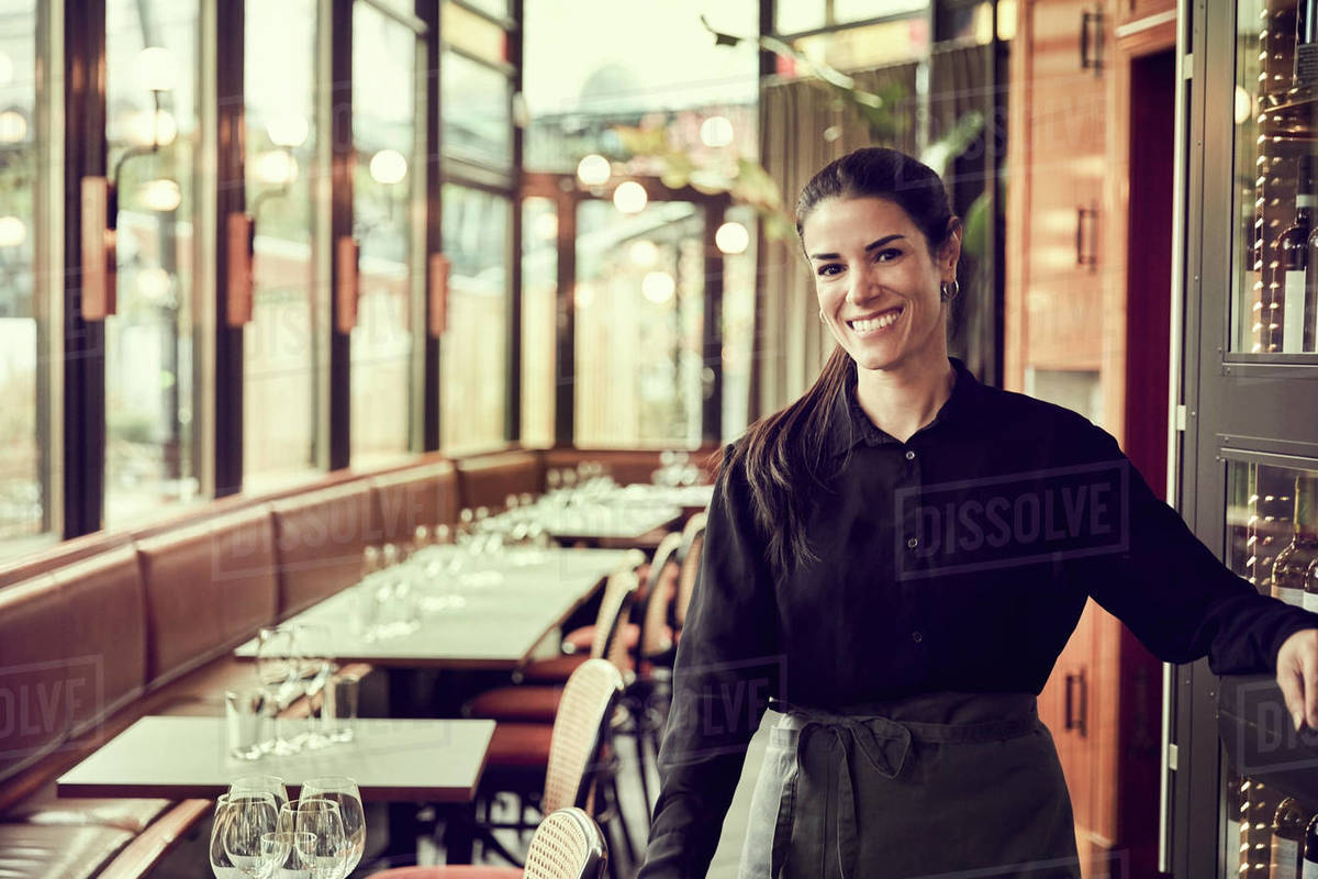 Portrait of smiling female owner standing in cafe Royalty-free stock photo