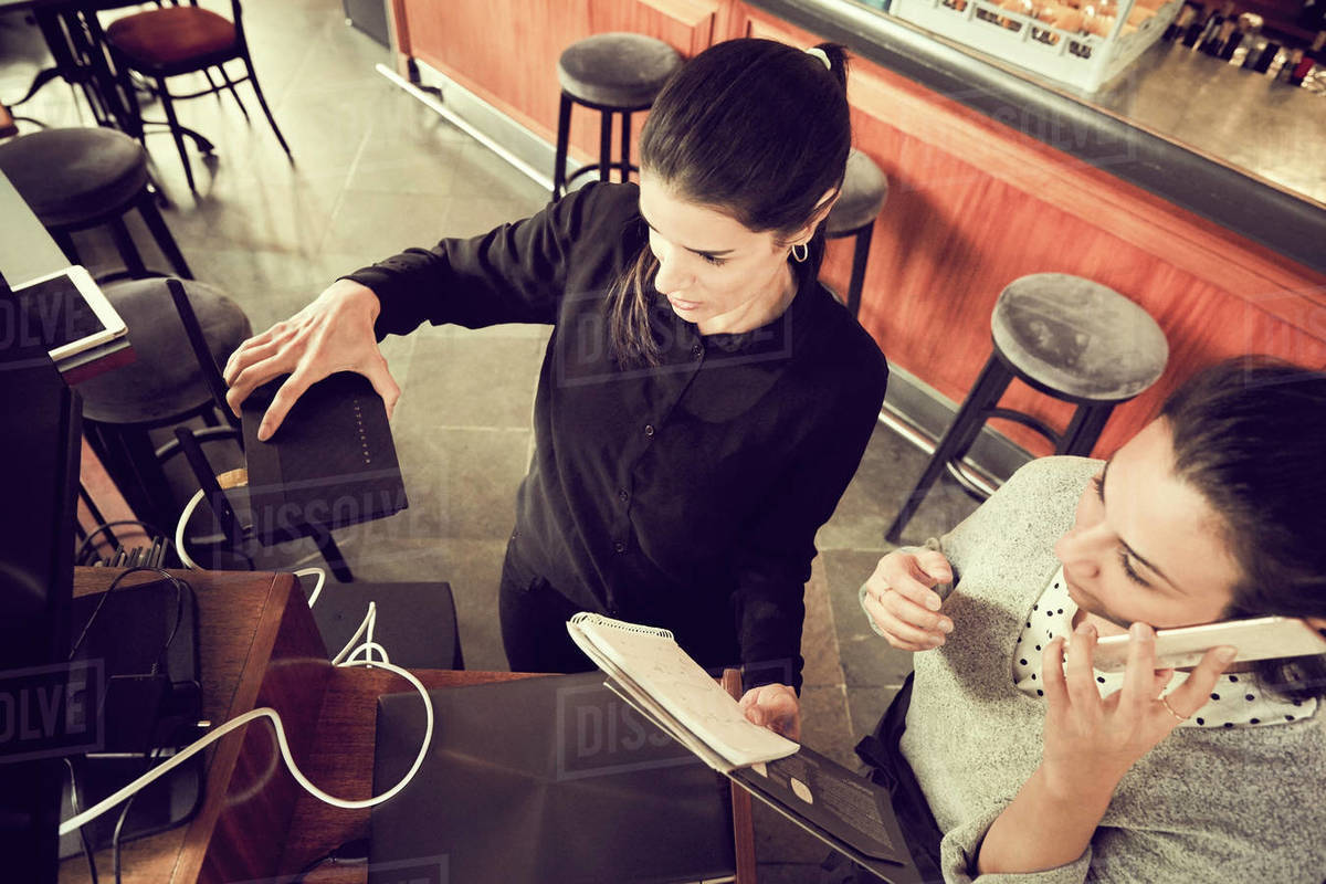 High angle view of owner holding modem while colleague talking through smart phone in cafe Royalty-free stock photo
