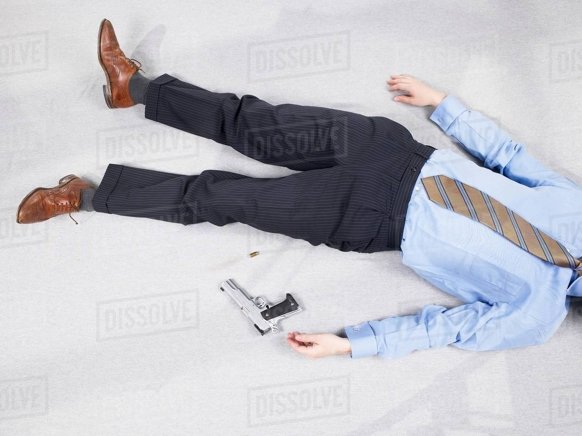 Man lying on floor with gun - Stock