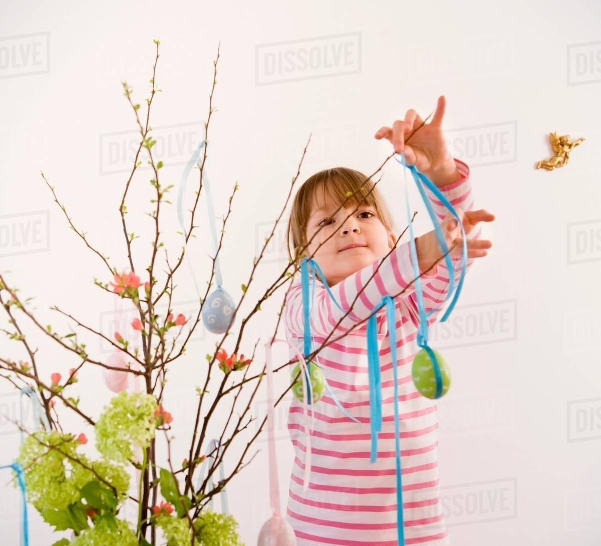 Girl decorating twigs for easter stock photo