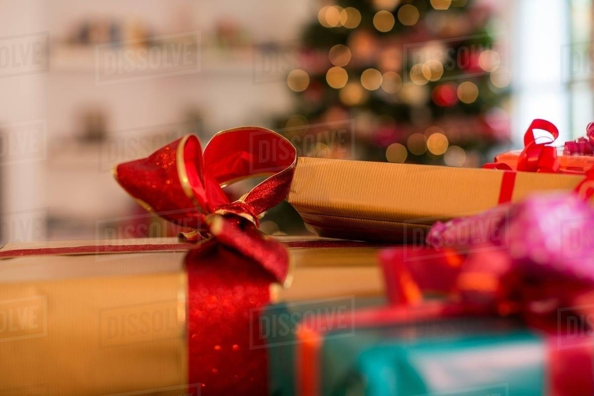 Close up of three christmas gifts with ribbons - Stock Photo - Dissolve
