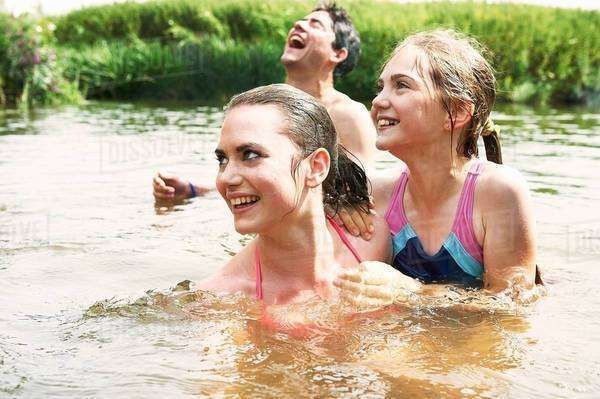 Two sisters and friend swimming in rural lake Royalty-free stock photo
