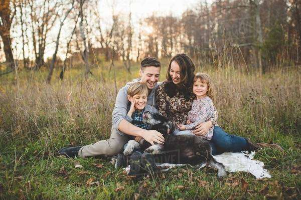Portrait of young couple with son, daughter and dog in field Royalty-free stock photo