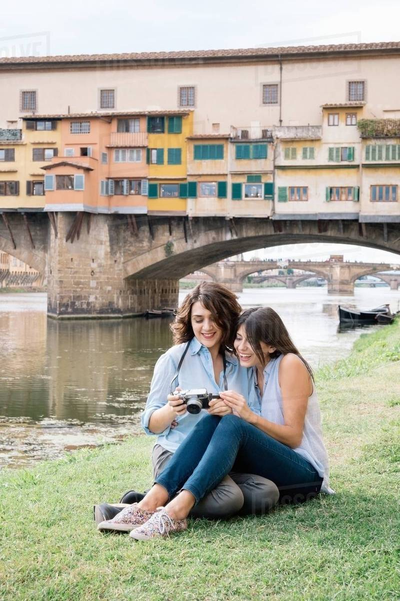 Camera A Ponte.Lesbian Couple Sitting Together Looking At Digital Camera In Front Of Ponte Vecchio Smiling Florence Tuscany Italy Stock Photo