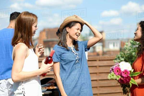 Female friends chatting and laughing at rooftop party Royalty-free stock photo