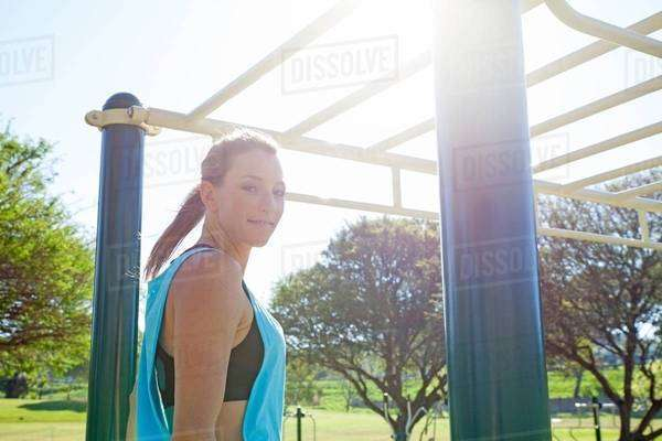 Mid adult woman preparing to train on monkey bars in park Royalty-free stock photo