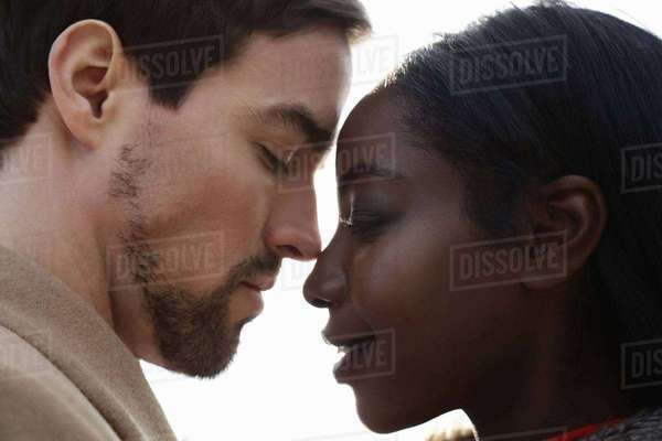 Multi ethnic couple, face to face, eyes closed, close-up Royalty-free stock photo