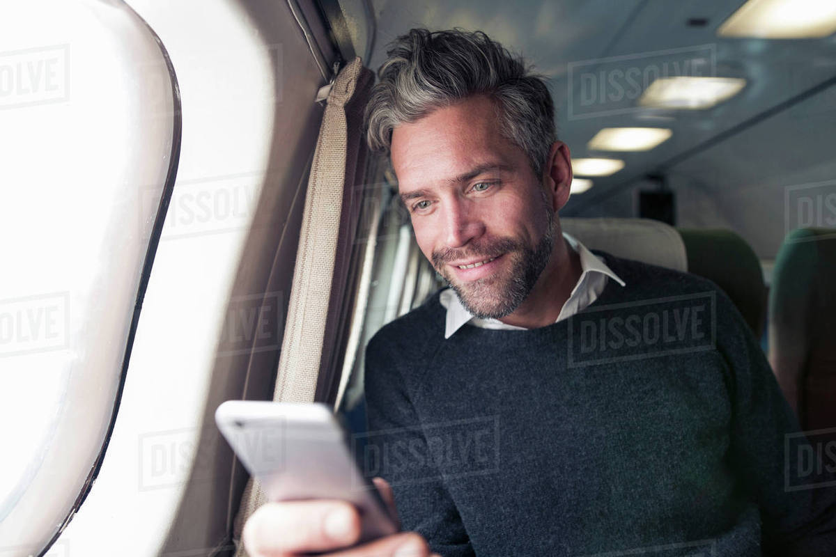 Mid adult man on airplane, using smartphone Royalty-free stock photo