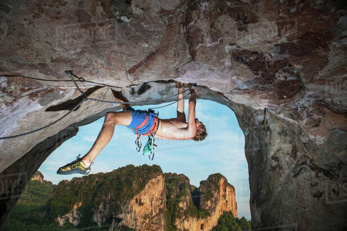 Rock Climber Climbing On Burnt Offerings Tonsai Railay Beach Krabi Thailand