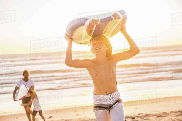 Boy on beach carrying surfboard over head Royalty-free stock photo