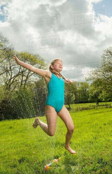 Young girl jumping over garden sprinkler in field Royalty-free stock photo