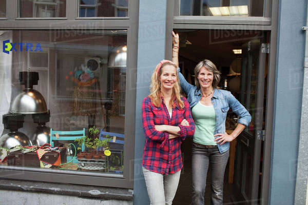 Women standing in shop doorway looking at camera smiling Royalty-free stock photo