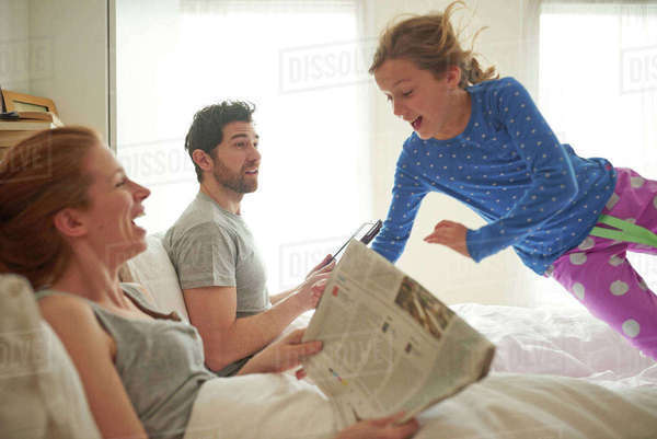 Mid adult couple reading broadsheet whilst daughter leaps on bed Royalty-free stock photo