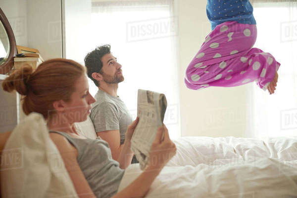 Mid adult couple reading broadsheet whilst daughter jumps on bed Royalty-free stock photo