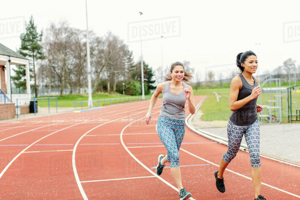 two young women running on running track stock photo dissolve
