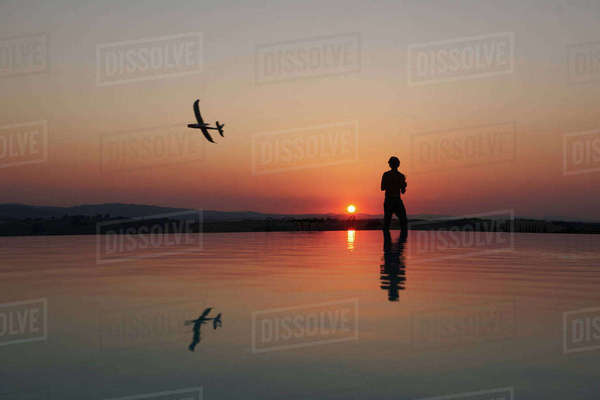Silhouetted man flying radio controlled airplane on sunset coast, Buonconvento, Tuscany, Italy Royalty-free stock photo