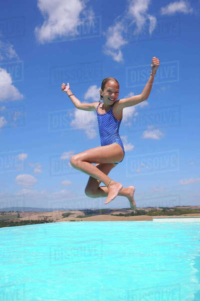 Girl jumping into swimming pool, Buonconvento, Tuscany, Italy Royalty-free stock photo