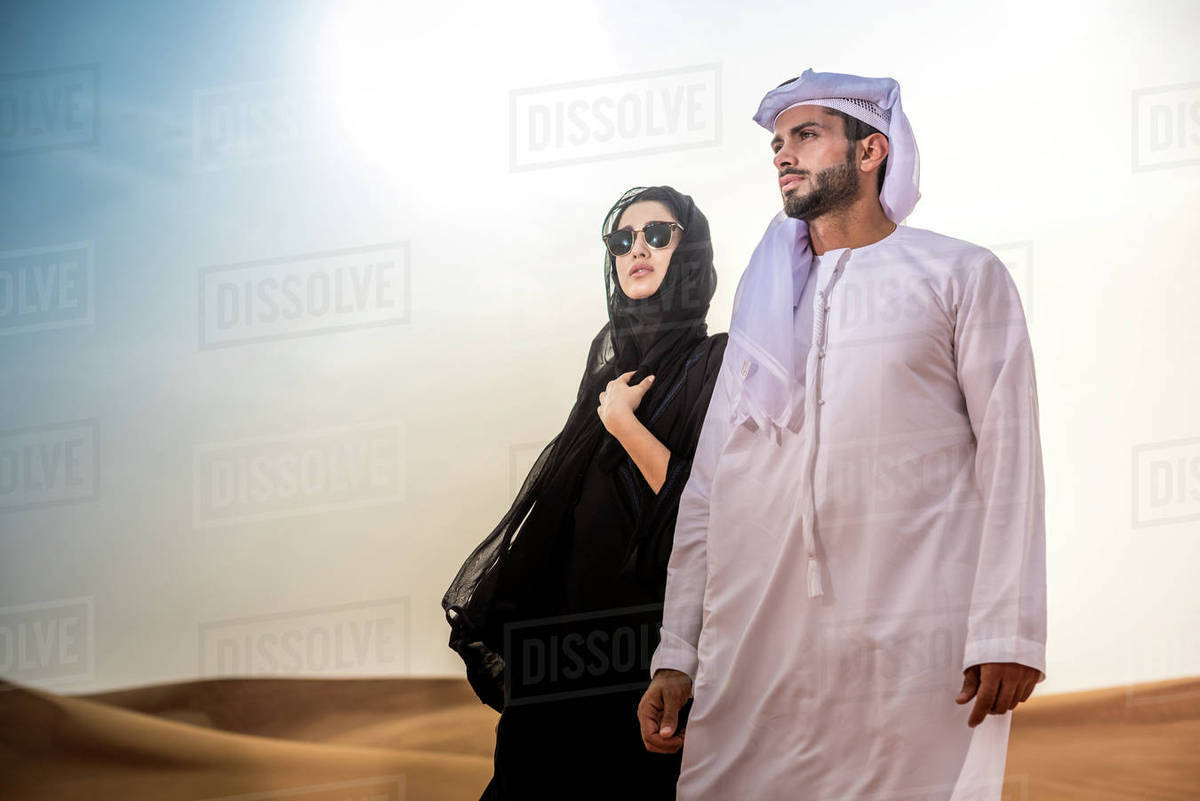 Couple wearing traditional middle eastern clothes in desert, Dubai, United  Arab Emirates stock photo