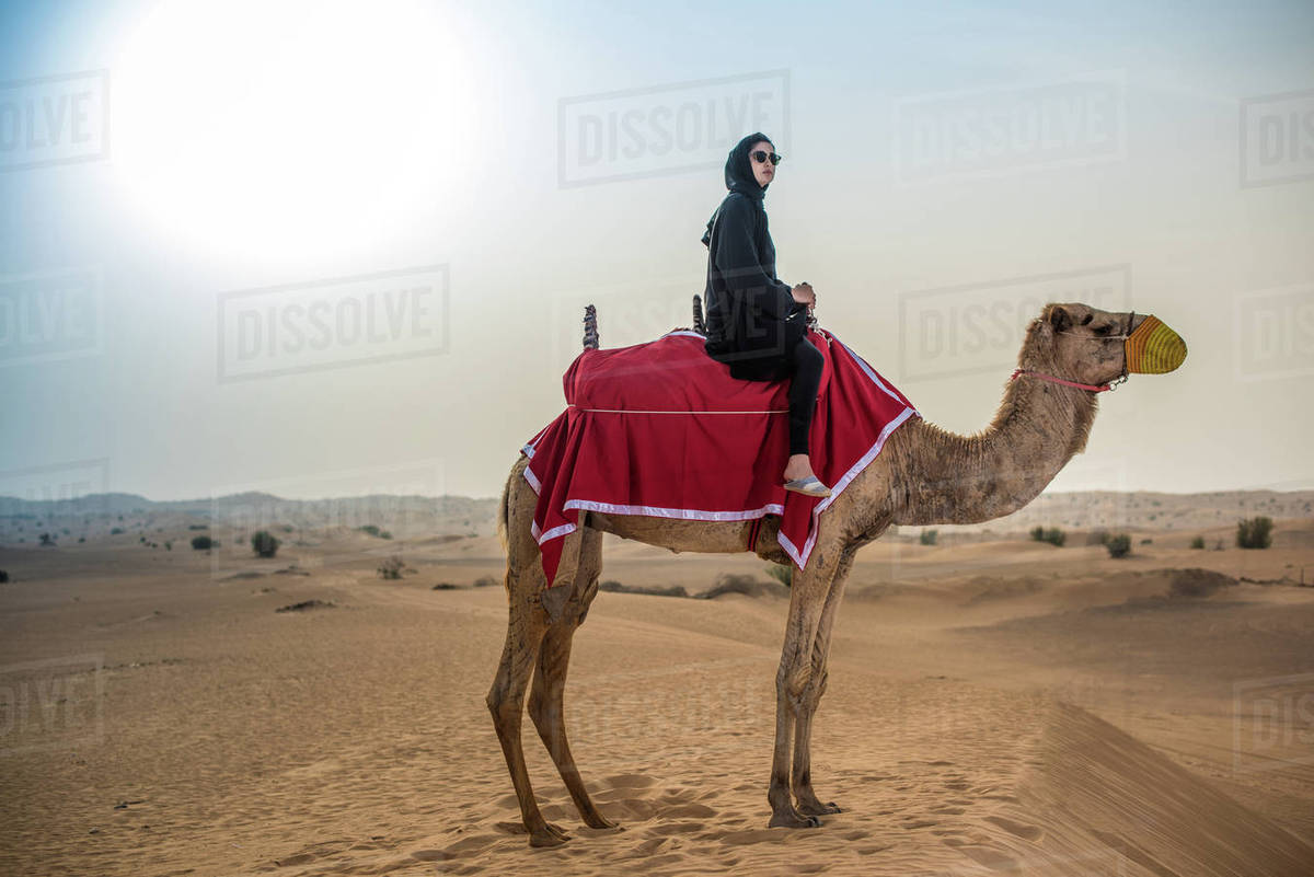 Young woman wearing traditional middle eastern clothes riding camel in  desert, Dubai, United Arab Emirates stock photo