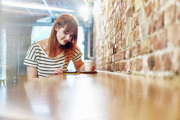 Female customer sitting at bench browsing digital tablet in coffee shop Royalty-free stock photo