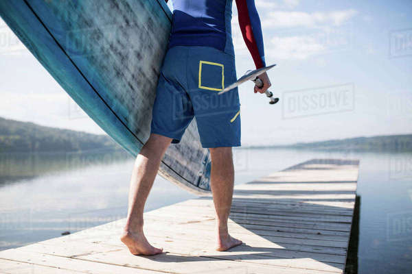 Waist down view of young man carrying paddleboard along pier, lake Pilsensee, Germany Royalty-free stock photo