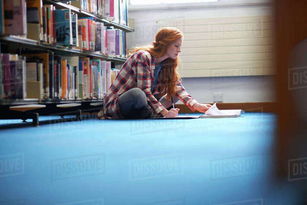 Young female college student writing notes on library floor Royalty-free stock photo