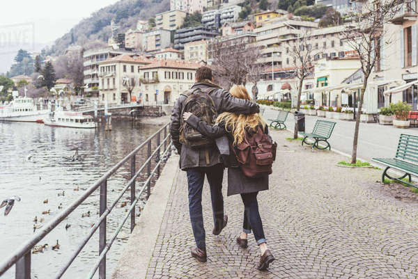Rear view of young couple strolling along lakeside, Lake Como, Italy Royalty-free stock photo