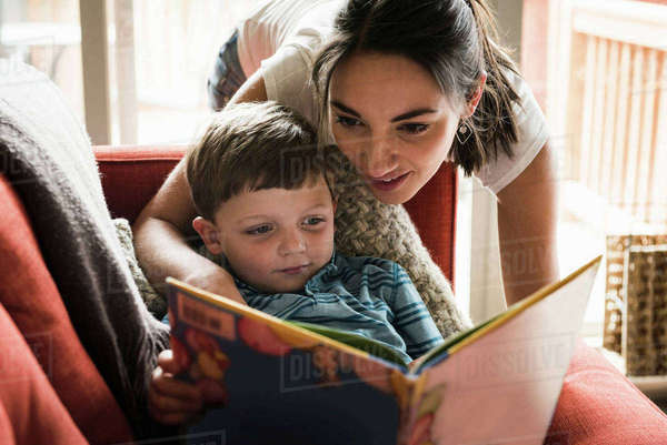 Mother teaching son to read book on sofa Royalty-free stock photo