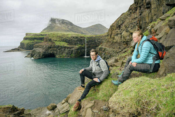 Hikers enjoying view from rocks, Gasadalur, Vagar, Faroe Islands Royalty-free stock photo