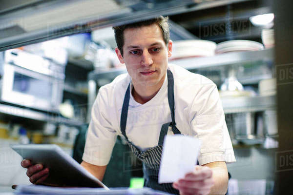 Young male chef using digital tablet and reading food order in kitchen Royalty-free stock photo
