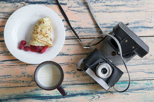 Still life of camera, pancake dessert and cup of milk, overhead view Royalty-free stock photo