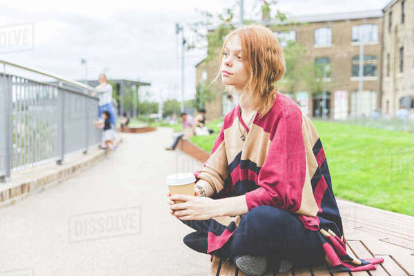 Woman holding cup sitting cross legged looking away, London, UK Royalty-free stock photo