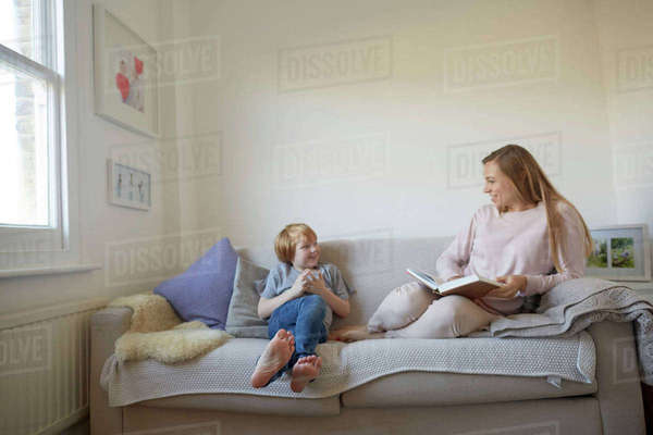Mid adult woman and son reading storybook on sofa Royalty-free stock photo