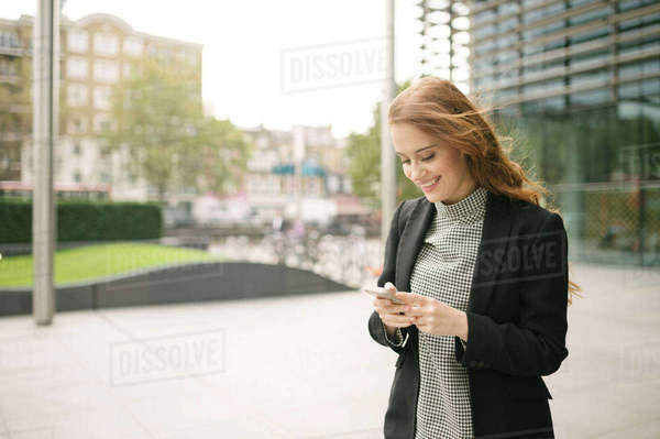 Woman in city looking at smartphone smiling Royalty-free stock photo