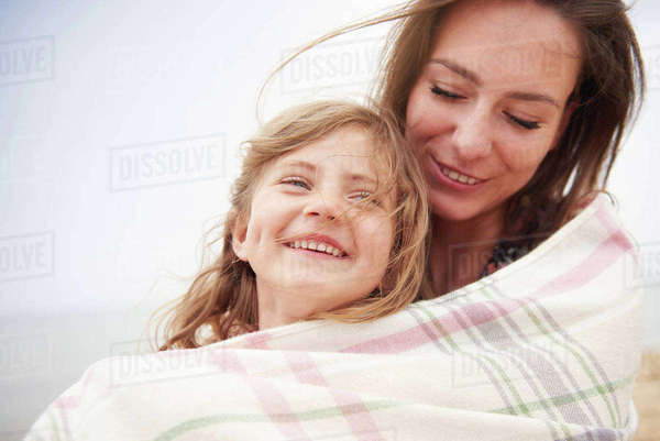 Happy mother and daughter wrapped in blanket Royalty-free stock photo