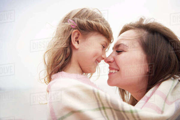 Happy mother and daughter wrapped in blanket, rubbing noses Royalty-free stock photo
