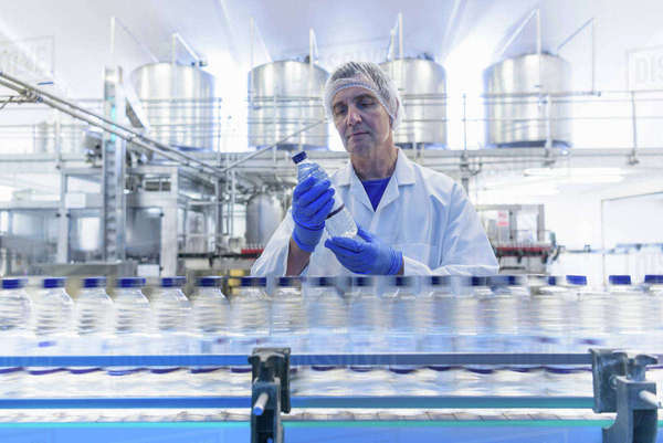 Worker inspecting water bottle on production line in spring water factory Royalty-free stock photo