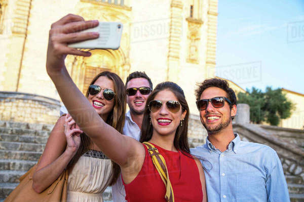 Two tourist couples in sunglasses taking selfie in front of church, Calvia, Majorca, Spain Royalty-free stock photo