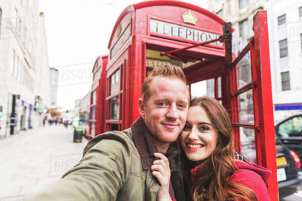 Couple taking selfie by telephone booth, London, UK Royalty-free stock photo